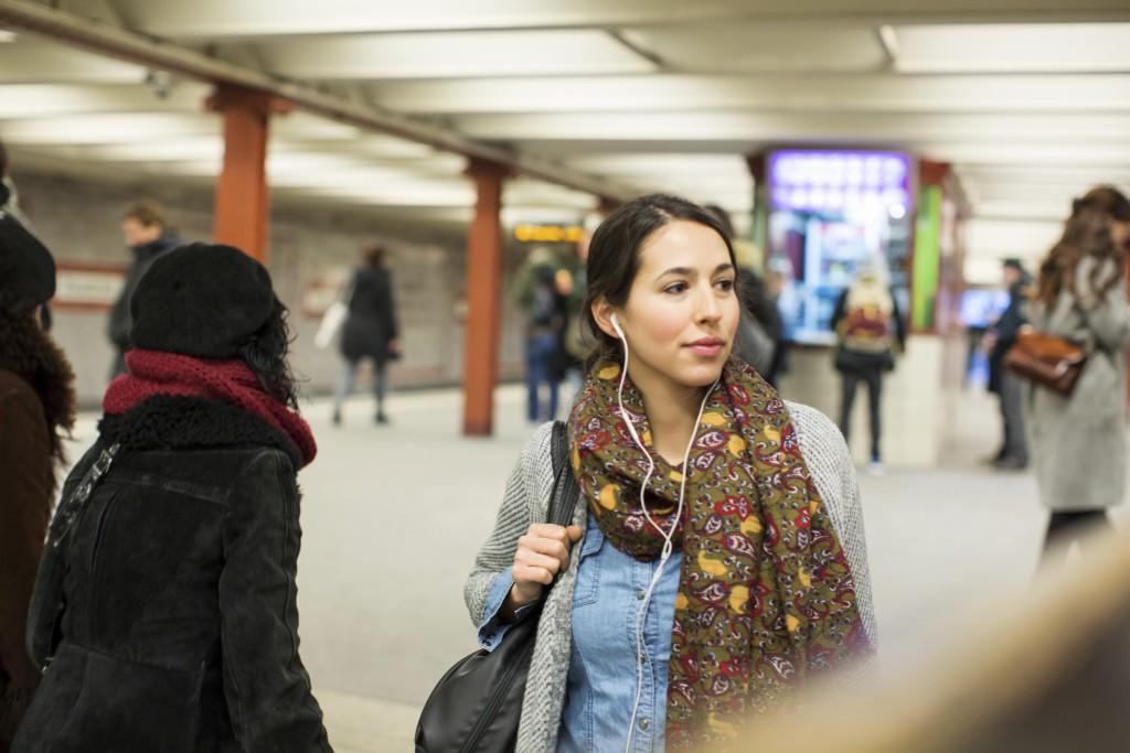 Frau mit Kopfhörern an der U-Bahn-Station
