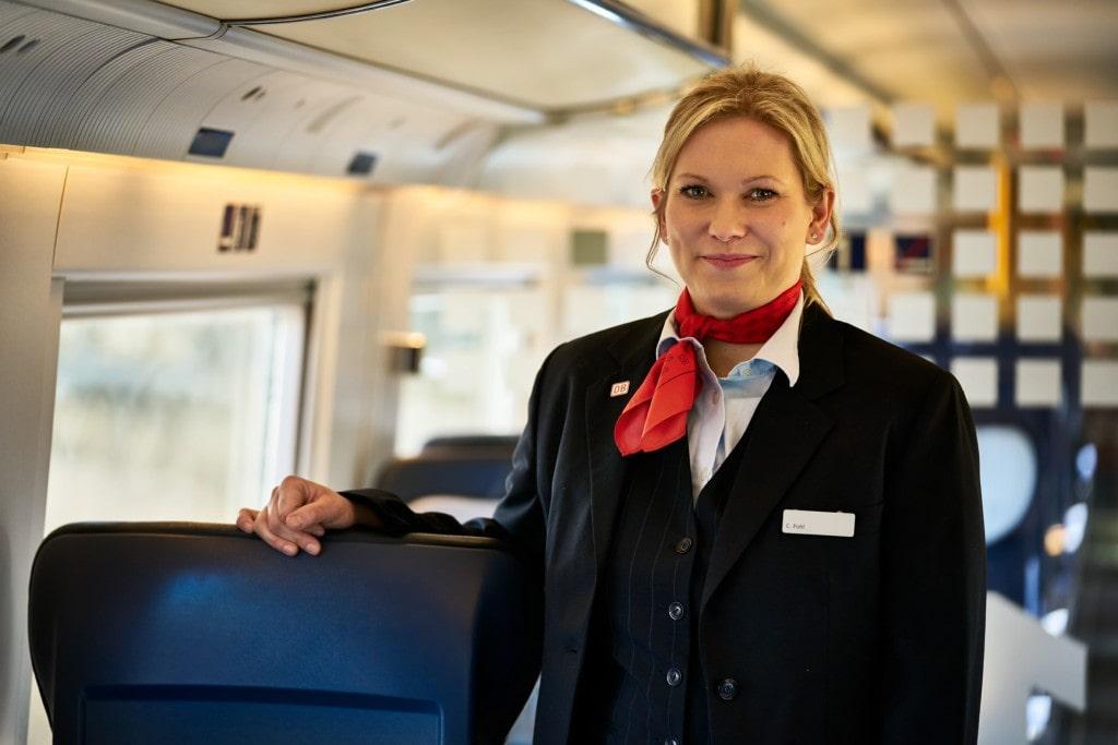Zugbegleiterin lächelt in die Kamera, Deutsche Bahn